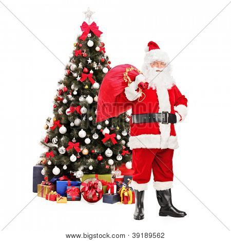Full length portrait of Santa Claus carrying a bag full of gifts on his back, christmas tree in the background