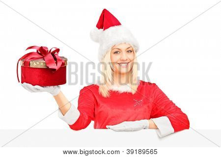 A female in santa costume standing behind a blank billboard and holding a present