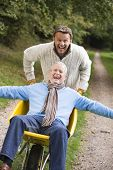 pic of senior-citizen  - Son pushing senior father in wheelbarrow - JPG