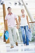 Couple In Shopping Mall With Bags