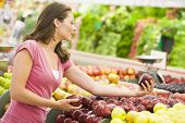 stock photo of grocery-shopping  - Woman shopping for apples at a grocery store - JPG
