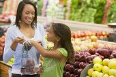 stock photo of grocery store  - Woman and daughter shopping for apples at a grocery store - JPG