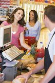 stock photo of hair integrations  - Women paying for purchases at a grocery store - JPG