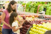 image of grocery-shopping  - Woman and daughter shopping for apples at a grocery store - JPG