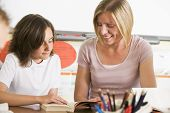 image of girl reading book  - Student in class reading book with teacher - JPG