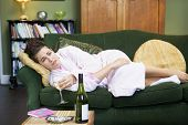 stock photo of saddening  - Young woman lying on sofa smoking and drinking wine - JPG