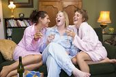 stock photo of slumber party  - Three woman in night clothes sitting at home drinking wine - JPG
