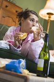 stock photo of housecoat  - Young woman at home drinking wine and eating potato chips - JPG