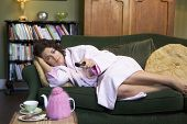 stock photo of housecoat  - Young woman lying on sofa at home watching television - JPG