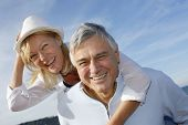pic of piggyback ride  - Portrait of cheerful senior couple having fun at the beach - JPG