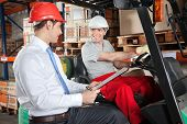 stock photo of forklift driver  - Happy forklift driver communicating with male supervisor at warehouse - JPG