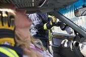 picture of crew cut  - Firefighter cutting out a windshield after an accident with injured woman in foreground  - JPG