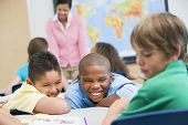 stock photo of misbehaving  - Students in class bullying student with teacher in background  - JPG