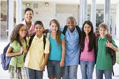 stock photo of tweeny  - Six students standing outside school with teacher - JPG