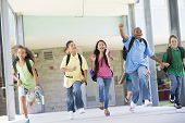 image of knapsack  - Six students running away from front door of school excited - JPG
