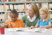stock photo of tutor  - Two students in class reading with teacher - JPG