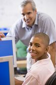 image of student teacher  - Teacher with male student in computer class - JPG