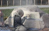 stock photo of sandblasting  - This sandblasting worker is engraving the lettering into the large stone monument - JPG