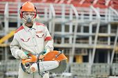pic of millwright  - construction worker in safety protective equipment with petrol disc cutter - JPG