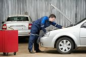 stock photo of internal combustion  - motor mechanic diagnosing automobile car engine before maintenance at repair service station - JPG