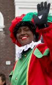 Zwarte Piet Waving To The Kids. He Is A Helper Of Dutch Saint Nicolaas