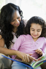 picture of mother child  - Mother and daughter in living room with book smiling  - JPG