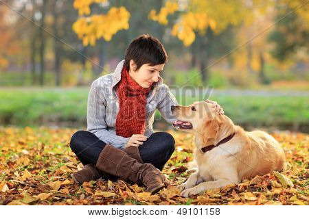 Young woman in a park stroking her retriever dog