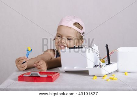 Girl fun holding a wrench nut, repairing toy