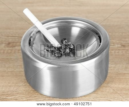 Metal ashtray and cigarette on wooden table
