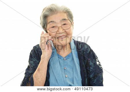 Old woman holding a mobile phone and talking