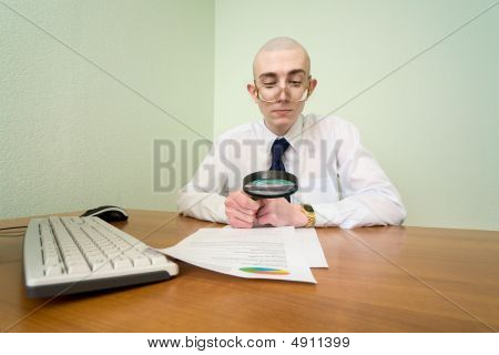 Boss With A Magnifier On A Workplace