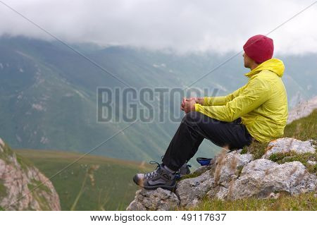 Man Hiker In Mountains Relaxing Sitting On Rocky Cliff With Clouds On Background