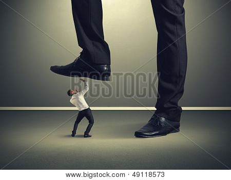 scared small businessman under big leg his boss