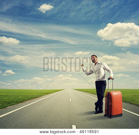 smiley young businessman hitch hiking on a road