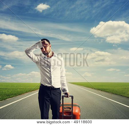 weary businessman with suitcase on a road