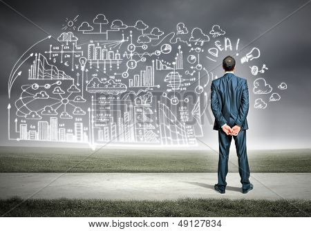 Back view image of young businessman standing against business sketch