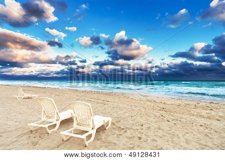 deckchairs on a beach on a background of ocean