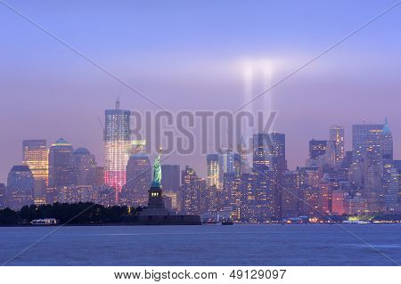 New York City Manhattan downtown skyline at night with statue of liberty and light beams in memory of September 11 viewed from New Jersey waterfront.