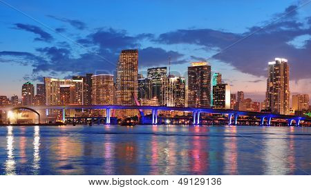Miami city skyline panorama at dusk with urban skyscrapers and bridge over sea with reflection