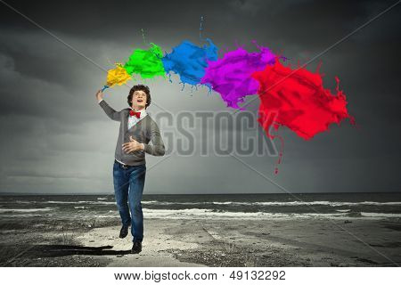 Young man with a splash coloured like a rainbow