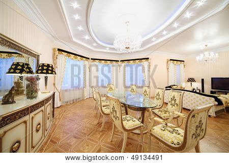 Living and dining room with luxury gilt furniture in classic style.