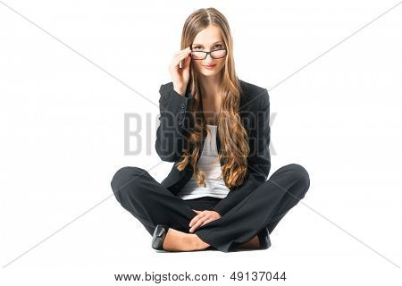 Young business woman with glasses in front of white background, sitting on the floor, maybe she is a businesswoman or lawyer scrutinizing