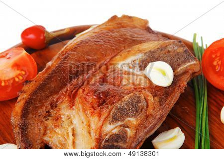 fresh grilled beef meat fillet on red wooden plate with tomatoes and capers isolated over white background