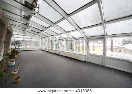 Spacious conservatory with small number of plants in cottage at winter.