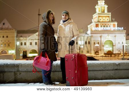 Young couple with big red trolley bag stands in evening against railway station