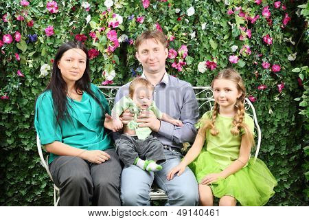 Happy family of four sit on white bench in garden near verdant hedge.