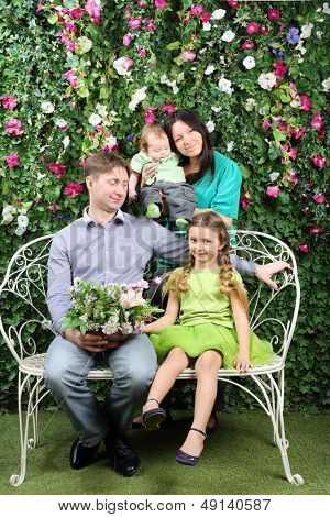 Happy family of four sit on white bench with bunch of flowers and stand behind in garden near verdant hedge.