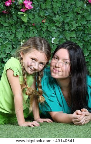 Smiling mother and little daughter lie on lawn in garden next to verdant fence.