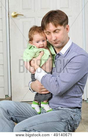 Father holds on hands crying baby and soothes next to white front door.