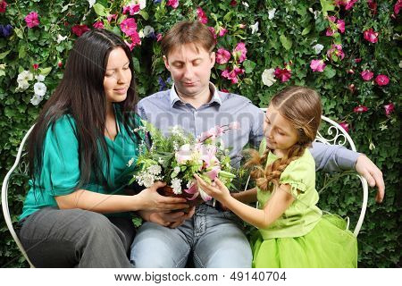 Happy family of three sit on white bench and hold flowers in garden near verdant hedge.